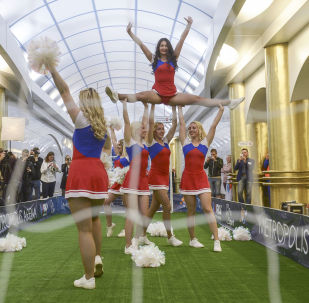 Girls from Cheerleading group perform before a football match on the platform of metro station of St. Petersburg subway