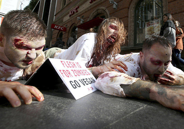 Members of People for the Ethical Treatment of Animals (PETA) dressed as zombies as they lay on the ground amid pedestrians in front of a fast food restaurant in Sydney, Thursday, April 15, 2017