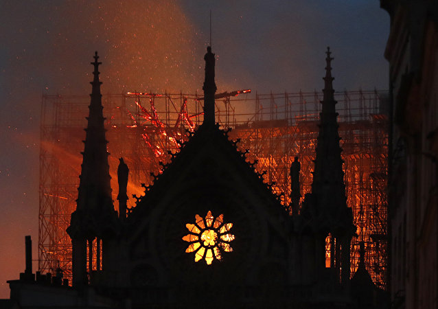 Flames and smoke rise from Notre Dame cathedral as it burns in Paris, Monday, April 15, 2019