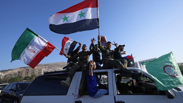 Syrian government supporters wave Syrian, Iranian and Russian flags as they chant slogans against U.S. President Trump during demonstrations following a wave of U.S., British and French military strikes to punish President Bashar Assad for suspected chemical attack against civilians, in Damascus, Syria, Saturday, April 14, 2018 - Sputnik Ελλάδα