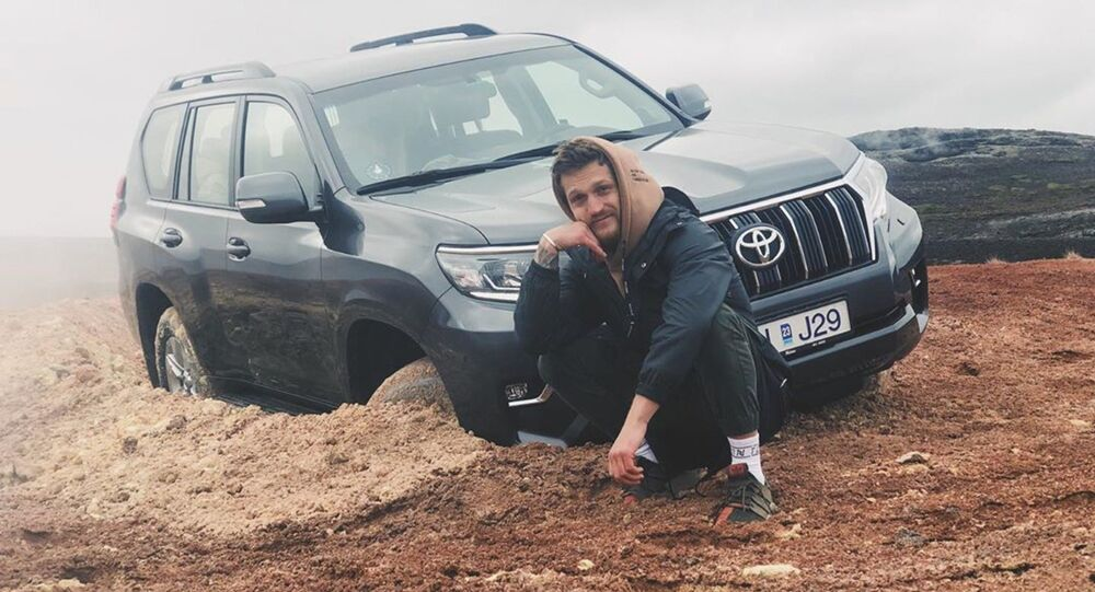 Alexander Tikhomirov, a Russian lifestyle blogger, poses near the off-roader stuck in clay