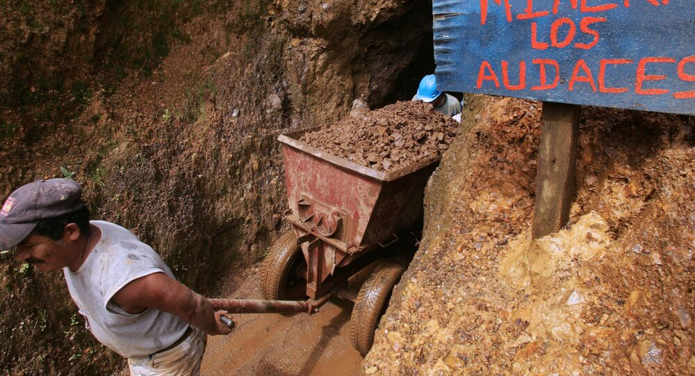 Independent miners extract ore from their shaft near Nambija, 460 kilometres south from Quito. (The sign at the shaft's entrance reads Mining Inc. the Bold Ones)