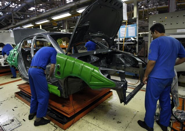 An Iranian man works on a Peugeot 206 car at the Iran Khodro auto plant, west of Tehran (File)